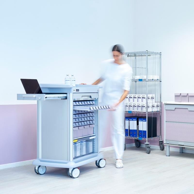 An operator in a nursing home removes an OTTAVIO therapy dispenser from a weekly patient specific tray, carried by a PRECISO therapy distribution trolley