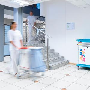 An operator in a nursing home pushes a CB20 bag holder trolley for dirty linen. with an ESSENTIAL patient hygiene trolley in the background.